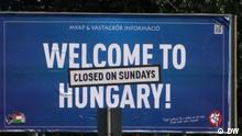 A billboard reads 'Welcome to Hungary! Closed on Sundays'