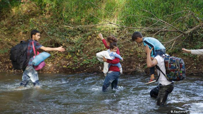 Refugees cross a river to enter Hungary