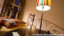 ILLUSTRATION - Ein Glas Wasser und Tabletten liegen am 22.06.2014 in Berlin auf einem Nachttisch während im Hintergrund ein Mann am Schlafzimmerfenster steht und in die Nacht schaut. Foto: Franziska Koark
