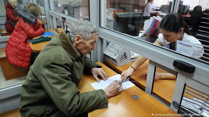 Пожилой россиянин получает пенсию в банке