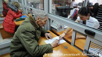 Пожилой мужчина возле окошка в банке