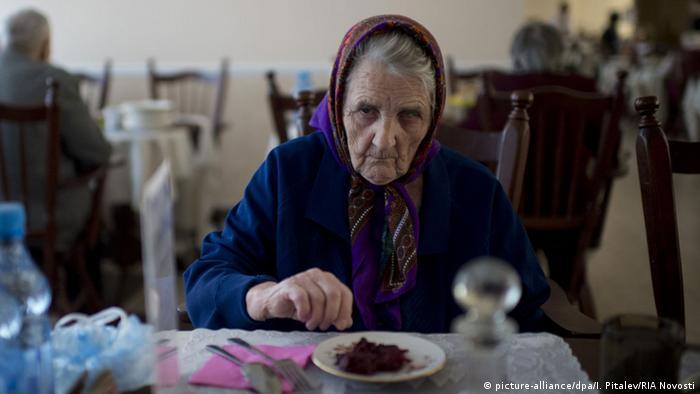 Пожилая женщина в России с тарелкой еды