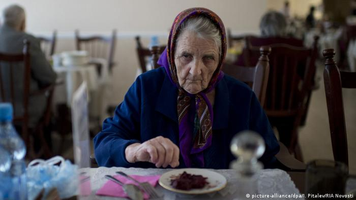 An old woman sits a table with a plate of food in front of her in Russia( picture-alliance/dpa/I. Pitalev/RIA Novosti)