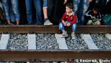 A migrant child sits on railway tracks at a train station in Tovarnik, September 18, 2015. REUTERS/Antonio Bronic