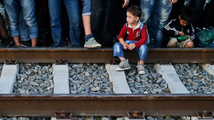 Mališan migranta sjedi na tračnicama