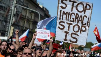 Protesters hold banners and Czech national flags during an anti-migrants rally in Prague