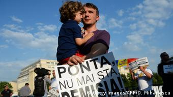 A man holds a poster reading 'Ponta, don't stay any longer, RESIGN!' during a protest asking the Prime Minister Ponta in Bucharest on June 5