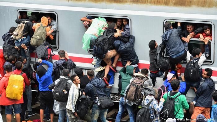 Беженцы пытаются влезть в переполненный поезд
