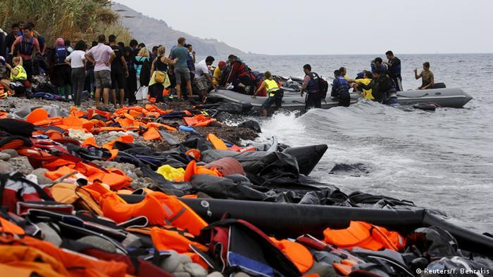 Беженцы и разбросанные по берегу спасательные жилеты на острове Лесбос