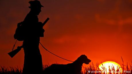 A hunter stands with his dog as the sun sets