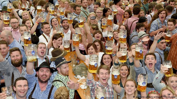 Lachende Menschen mit Bierkrügen auf dem Oktoberfest in München