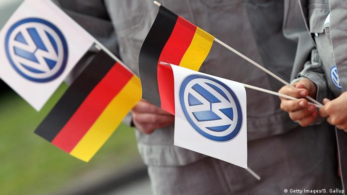 Workers hold German and Volkswagen logo flags at Wolfsburg, Germany