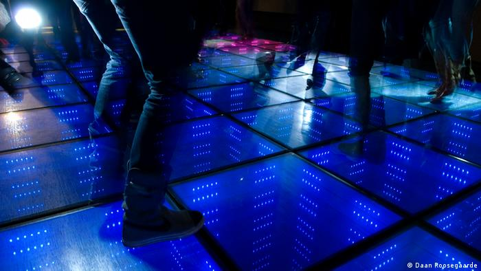 People photographed from the thigh down dance on an electric blue dancefloor which is powered by the kinetic energy from their movements
