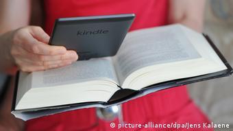 Eine Fau mit einem eReader und einem Buch in den Händen