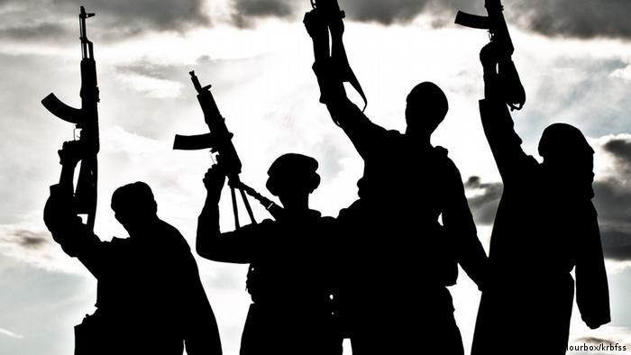 A silhouette of several militant with rifles
