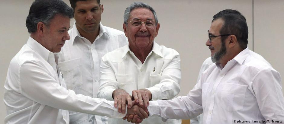 Raúl Castro (c.), presidente colombiano, Juan Manuel Santos (esq.), e líder guerrilheiro Rodrigo Londoño
