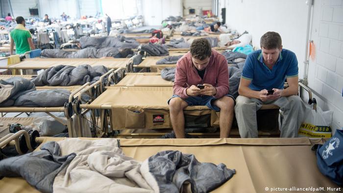 refugees in stuttgart using smartphones (photo: Marijan Murat/dpa).