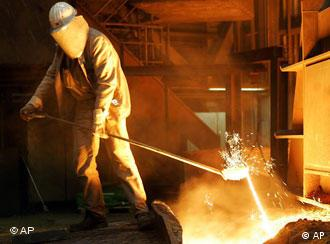 A Chinese steel worker labors at Shougang Steel company in Beijing, China