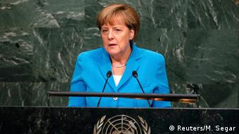 Angela Merkel speaking at microphone, dressed in blue