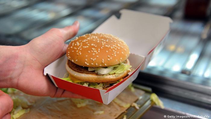 An employee prepares a Giant hamburgers at a US fast food Mac Donalds restaurant