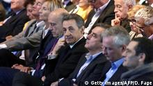 Head of French right-wing party Les Republicains and former President Nicolas Sarkozy (4th R) looks on as he sits next to Les Republicains' party member and Mayor of Bordeaux Alain Juppe (5th R), Les Republicains party member and Former French Prime Minister Francois Fillon (3rd R), UDI-MoDem's chief candidate for the Ile de France region and MoDem vice-President Marielle de Sarnez (6th R) and Les Republicains' party member Bruno Le Maire (2nd R) during a campaign meeting of the Les Republicains' candidate for the December regional elections in Ile-de-France on September 27, 2015, in Nogent-sur-Marne, near Paris. AFP PHOTO / DOMINIQUE FAGET (Photo credit should read DOMINIQUE FAGET/AFP/Getty Images)