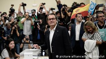 Лидер сепаратистов Артур Мас бросает бюллетень в урну для голосования во время выборов 27 сентября