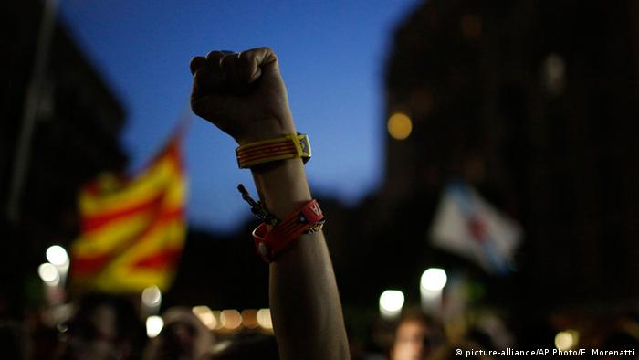 Поднятая вверх рука, сжатая в кулак, с браслетами сторонников сепаратистов