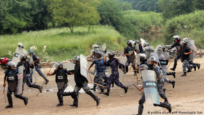 Nepalese policemen run for cover as they are chased by protestors belonging to ethnic and religious groups dissatisfied with Nepal's new constitution adopted on Sunday, in Birgunj, a town bordering India in Nepal, Thursday, Sept. 24, 2015 (AP Photo/ Jiyalal Sah)