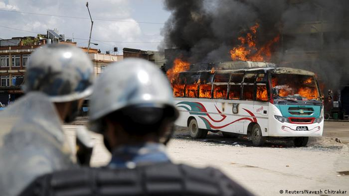 Police stand in front of a burning passenger bus after it was set on fire by unidentified protesters during the nationwide strike, called by the opposition parties against the proposed constitution, in Kathmandu, Nepal September 20, 2015 (Photo: REUTERS/Navesh Chitrakar)