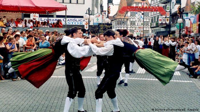 Dois homens e duas mulheres vestidos com trajes tradicionais alemães dançam na Oktoberfest de Blumenau