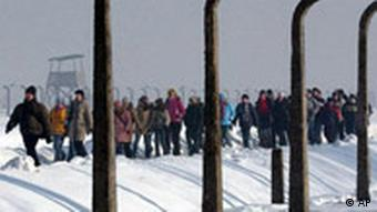 A column of people walking through the grounds of the former Nazi concentration camp at Auschwitz