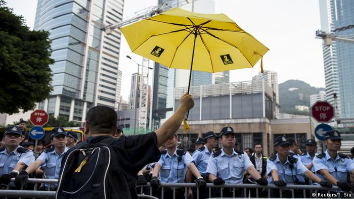 A man in Hong Kong holds a yellow umbrella, the sign of a pro-democracy movement
