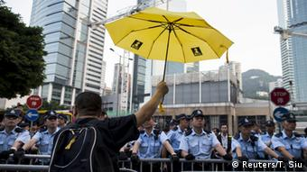 A pro-democracy protester rises a yellow umbrella, the symbol of the Occupy Central movement, in front of a line of policemen during a rally outside government headquarters in Hong Kong, China September 28, 2015 (Photo: REUTERS/Tyrone Siu)
