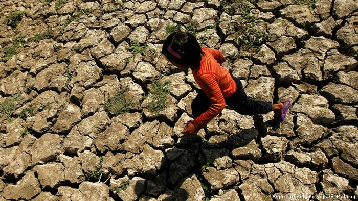 A child walks over drought-cracked land