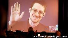 ARCHIV - Der NSA-Enthüller Edward Snowden winkt am 14.12.2014 in Berlin während einer Videoschalte dem Publikum zu. Foto: Wolfgang Kumm/dpa (zu dpa Spionage-Enthüller Snowden twittert jetzt vom 29.09.2015) +++(c) dpa - Bildfunk+++