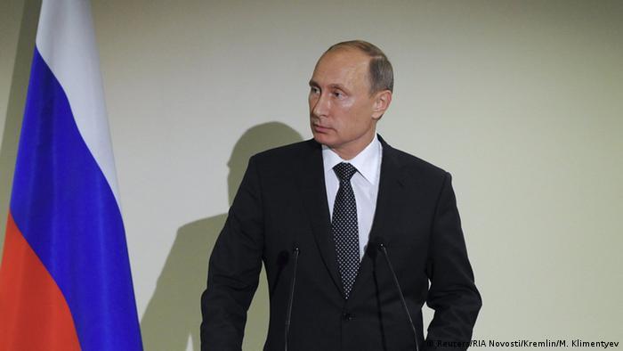 Президент России Владимир Путин рядом с флагом страны