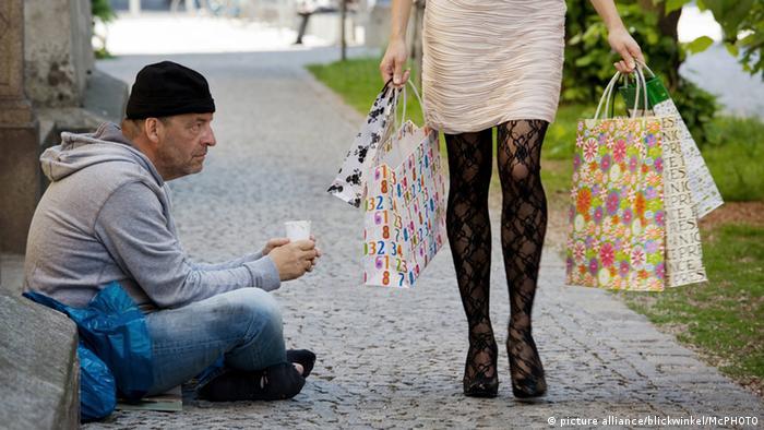 Pedinte ao lado de mulher com sacolas de compras na Alemanha
