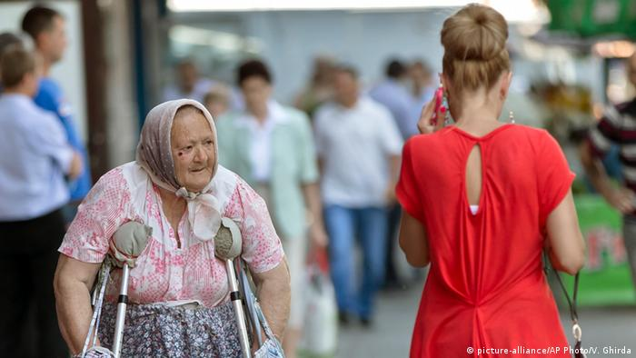 Бабушка на костылях и богато одетая молодая девушка