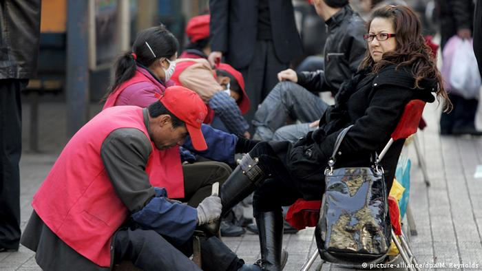 A woman having her shoes shined in China