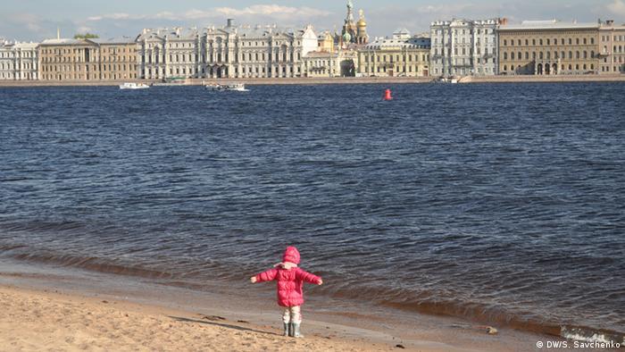 Russland Stadt Sankt-Petersburg, Stadtstrand am Newa, ein kleindes Mädchen steht am Stadtstrand und guckt ins Wasser