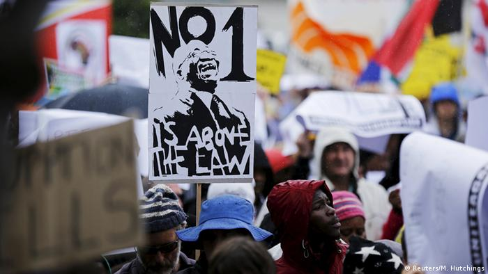 Demontrators at an anti-corruption protest holding up a placard with a cartoon of Zuma stating no one is above the law