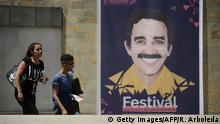 People walk near a poster depicting late Nobel Literature Prize laureate Gabriel Garcia Marquez -- in Medellin, Antioquia department, Colombia, on September 29, 2015, on the opening day of the III edition of the Gabriel Garcia Marquez Journalism Award that recognizes the best of Ibero-American journalism. The Nobel-winning novelist, author of the groundbreaking epic One Hundred Years of Solitude, died in Mexico City in April 2014, at the age of 87. AFP PHOTO / RAUL ARBOLEDA (Photo credit should read RAUL ARBOLEDA/AFP/Getty Images)