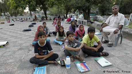 Kinder sitzen auf Boden in Park (Foto: REUTERS/Caren Firouz)