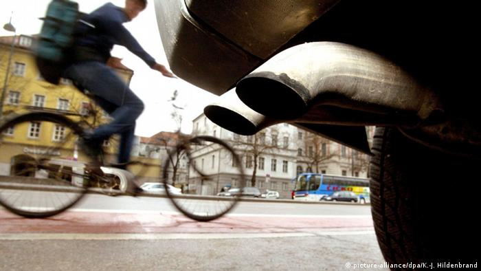 Car exhaust pipe in front of biker on street (picture-alliance/dpa/K.-J. Hildenbrand)