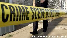 ARCHIV - ILLUSTRATION - Ein us-amerikanischer Polizist läuft am 13.08.2007 in der Nähe eines Tatorts hinter einem Absperrband entlang. EPA/LARRY W. SMITH (zu dpa US-Todesschütze von Austauschschüler aus Hamburg angeklagt vom 29.04.2014) +++(c) dpa - Bildfunk+++
