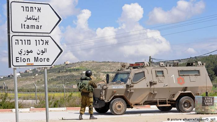 A tank at a checkpoint in the West Bank, with road signs pointing to Israeli settlement Itamar. (Photo: UPI/Debbie Hill /LANDOV)