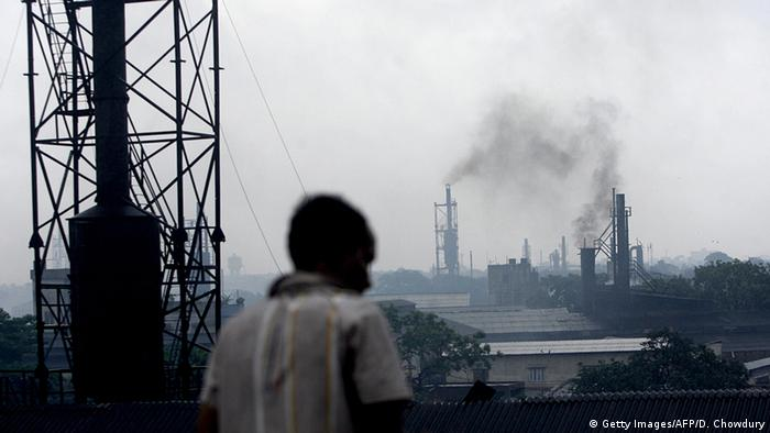 An Indian bystander watches as smoke rises from a cast iron factory at Howrah on the outskirts of Kolkata