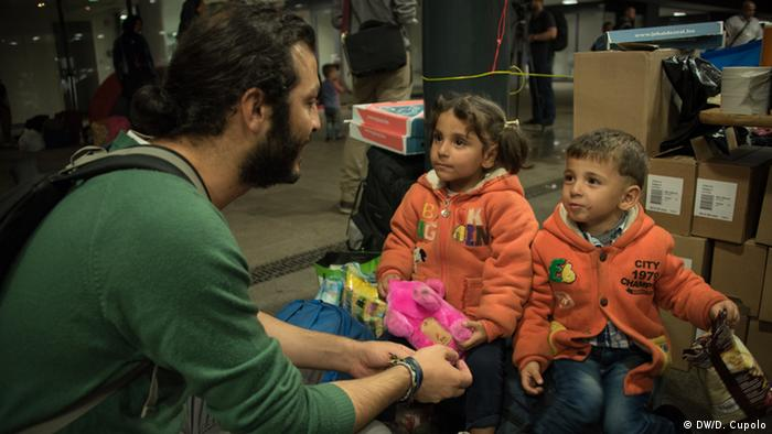 Yahya Abdullah kneels in front of two children at Keleti Station