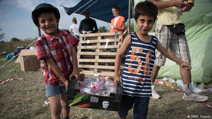Children leave a distribution tent with a box of water bottles in Tovarnik