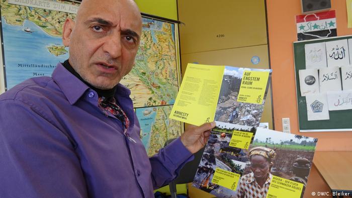 Aziz Fooladvand holding up Amnesty International pamphlets. (Photo: Carla Bleiker/ DW)
